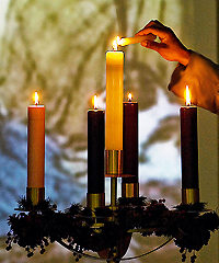 Advent Wreath with Candles Lit, With Hand of Person in Robe Lighting Center Candle