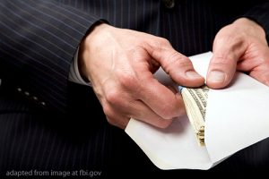 File Photo of Arms and Hands of Man in Business Suit Taking Cash from Envelope, adapted from image at fbi.gov