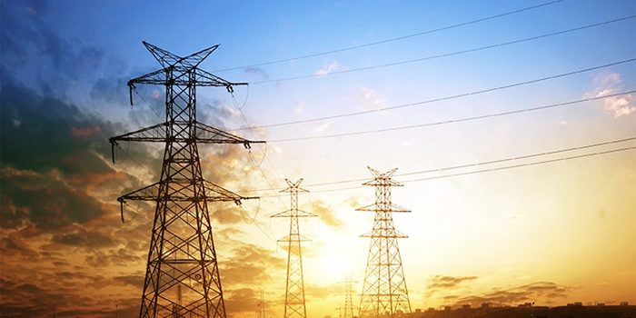 File Photo of Electrical Power Lines in Countryside with Sunset in Background, adapted from image at energy.gov