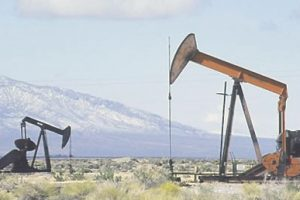 File Photo of Oil Wells with Mountains in Background, adapted from image at blm.gov by Steven C. Welsh www.stevencwelsh.info :: www.stevencwelsh.com