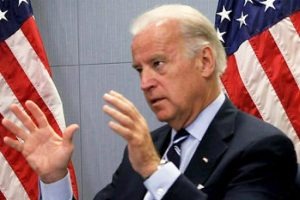 File Photo of Joe Biden, Mostly Turned to the Side, Gesturing with Both Hands, with U.S. Flags in the Background, adapted from image at ar.usembassy.gov